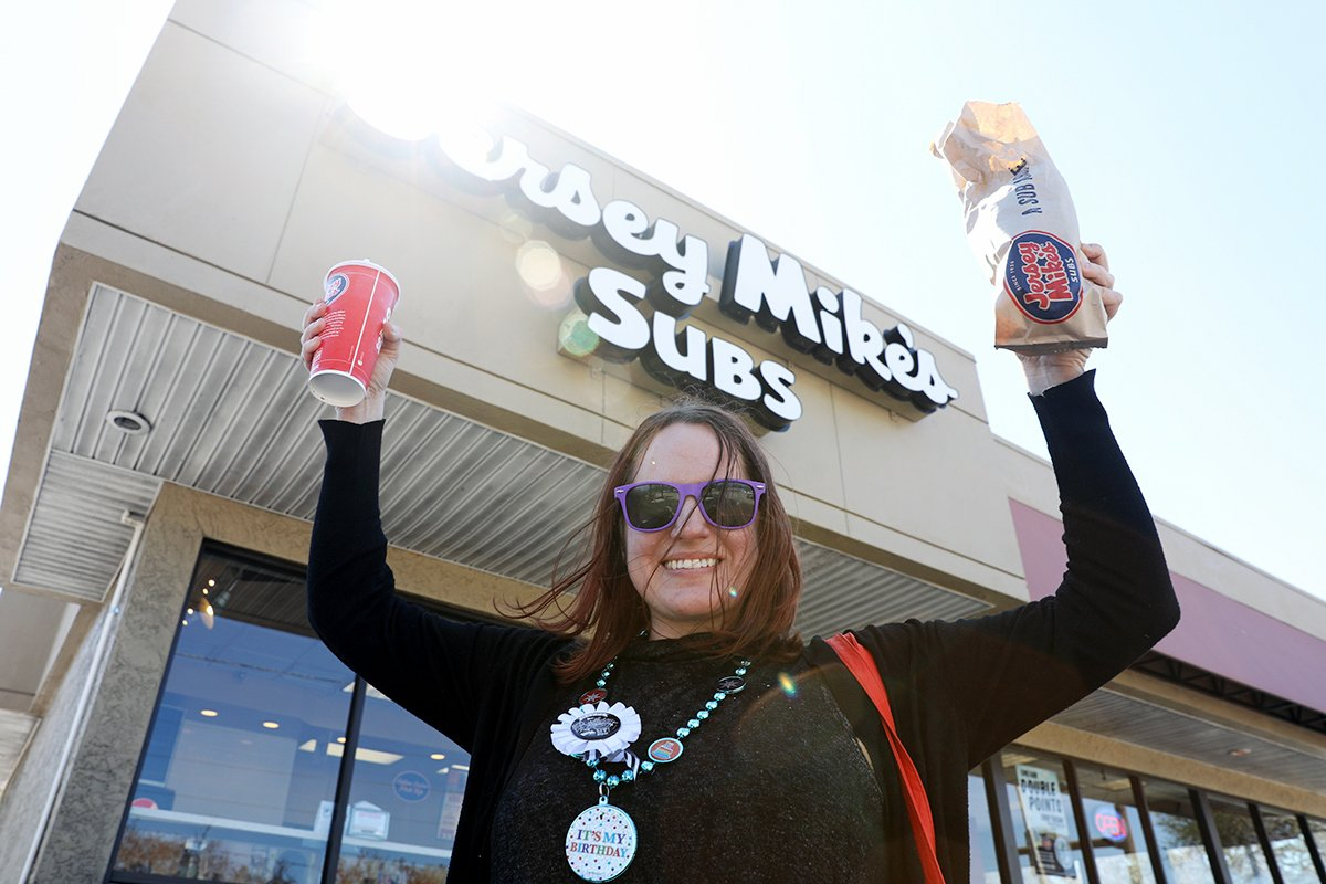 A woman smiles as she holds up a drink and a sub she got for free from Jersey Mike's Subs.