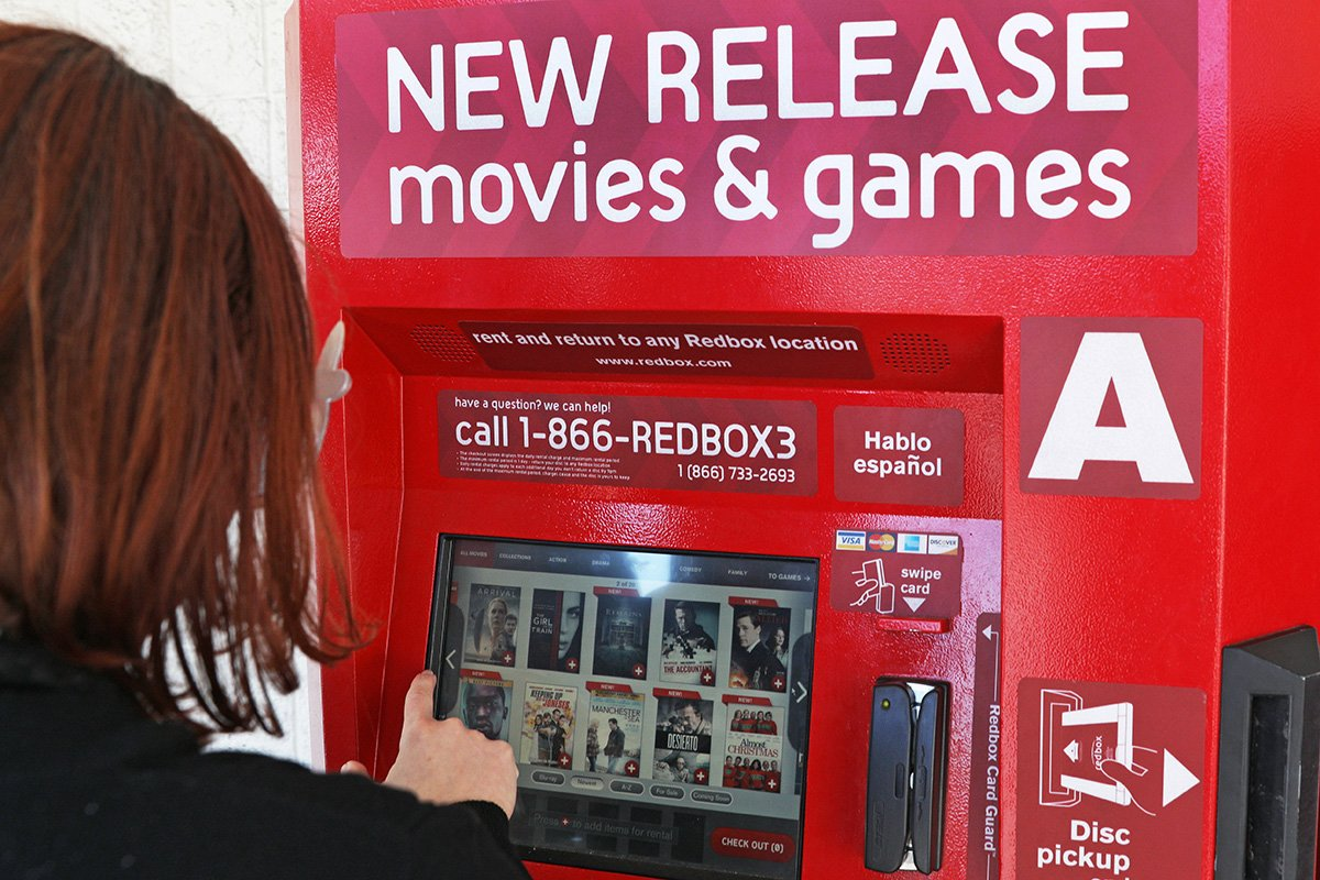 A person selects a movie from a red box.