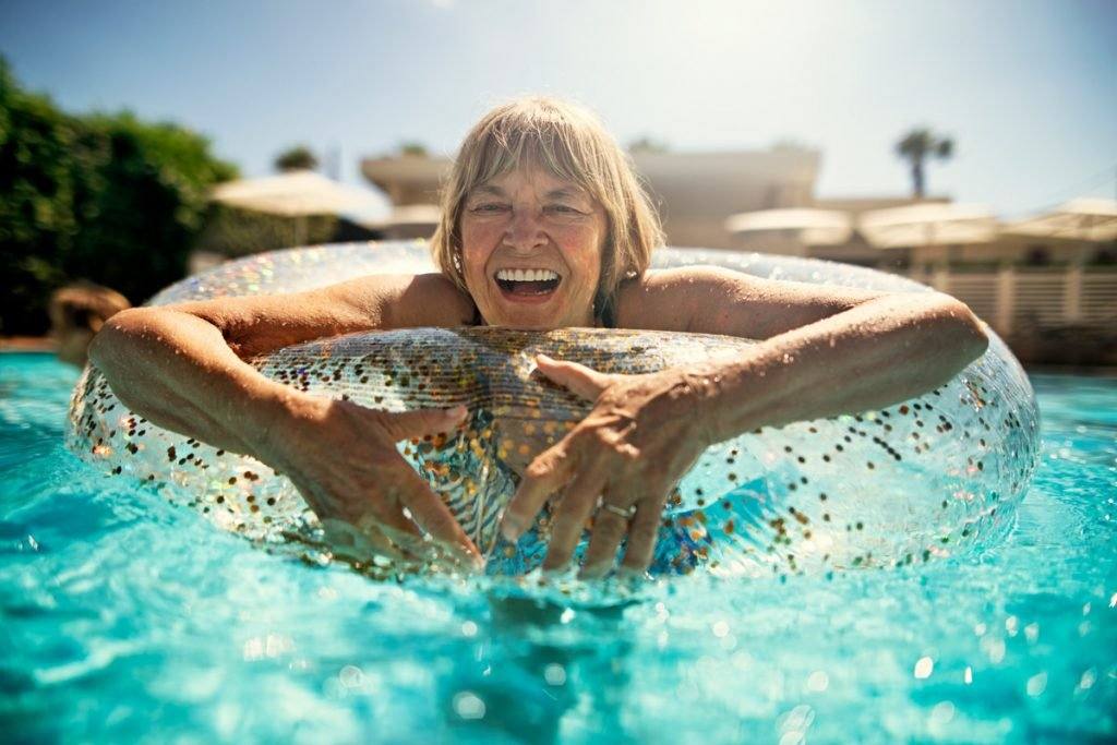 A retired woman floats in a circular floating device in a swimming pool.
