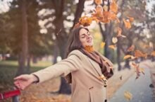 A woman wearing a brown coat and scarf smiles as she throws fall leaves around herself